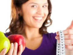 Health coach holding a measuring tape and fruit.