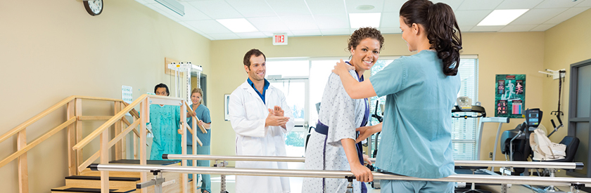 A DPT supervising his PT assistant while she supports patient during a balance modality.
